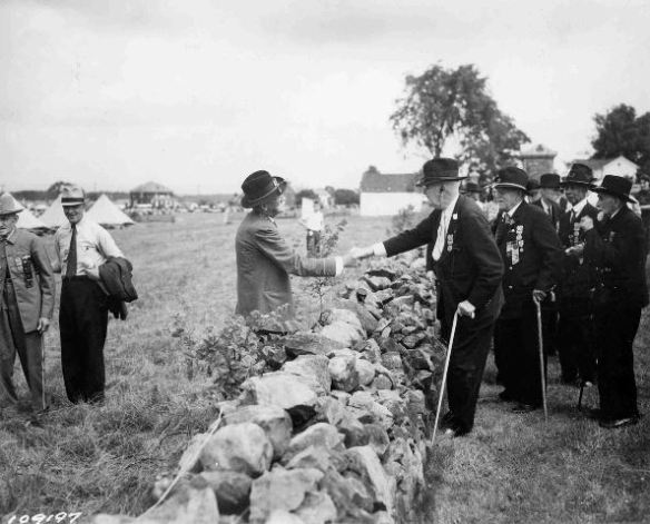In what's become an iconic photo representative of the 1913 Reunion, a Union and a Confederate veteran join hands across the stone wall at the High Water mark. Photo Courtesy: Adams County Historical Society.