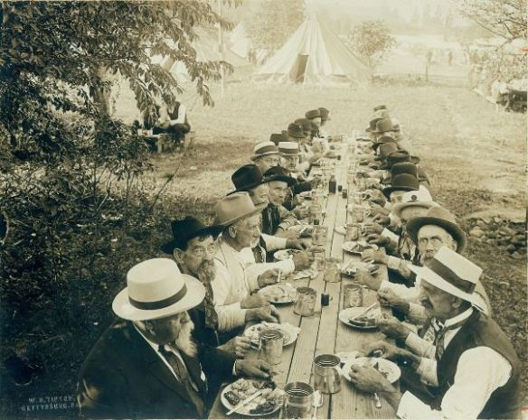 Veterans break bread together in this iconic 1913 photo taken by Reunion photographer W.H. Tipton. Photo Courtesy: Adams County Historical Society.